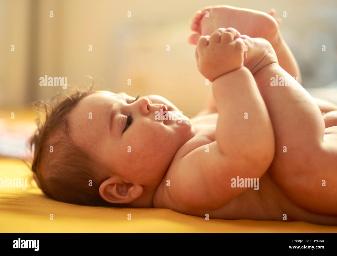 Baby boy playing with feet - Stock Image