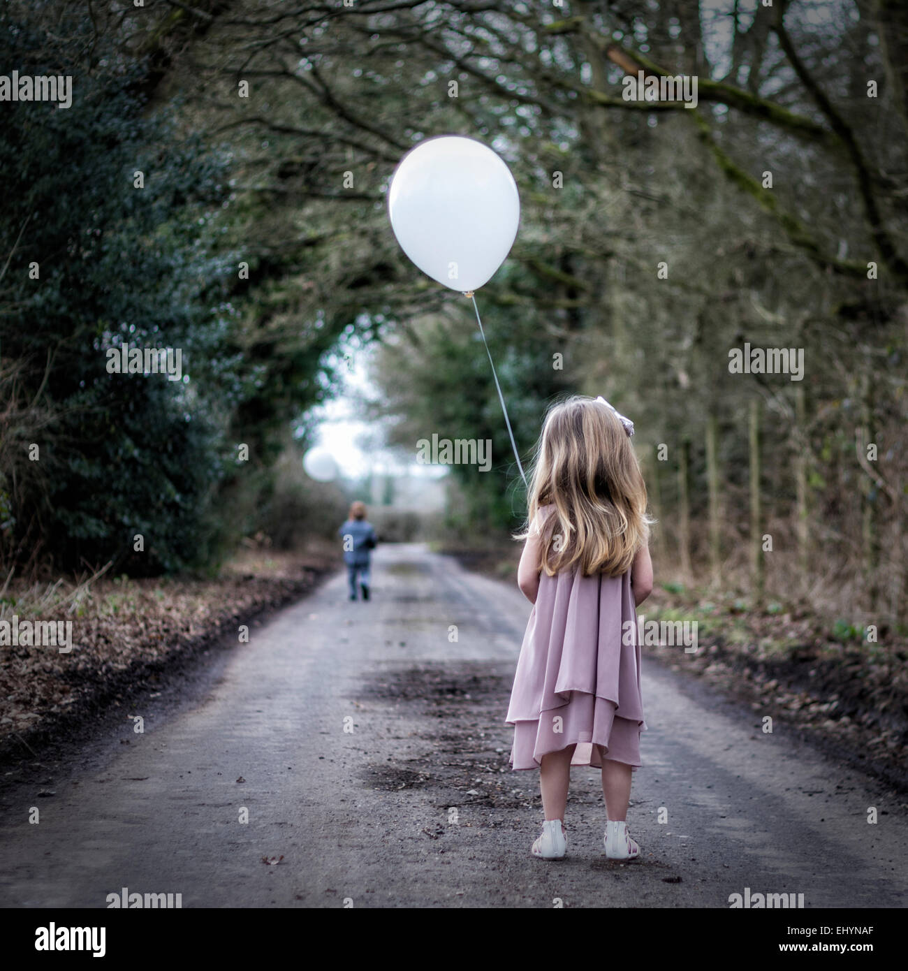 Rear view of girl holding a balloon looking at boy running away from her - Stock Image