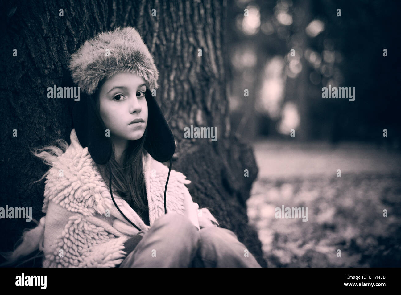 Sad girl leaning against a tree - Stock Image