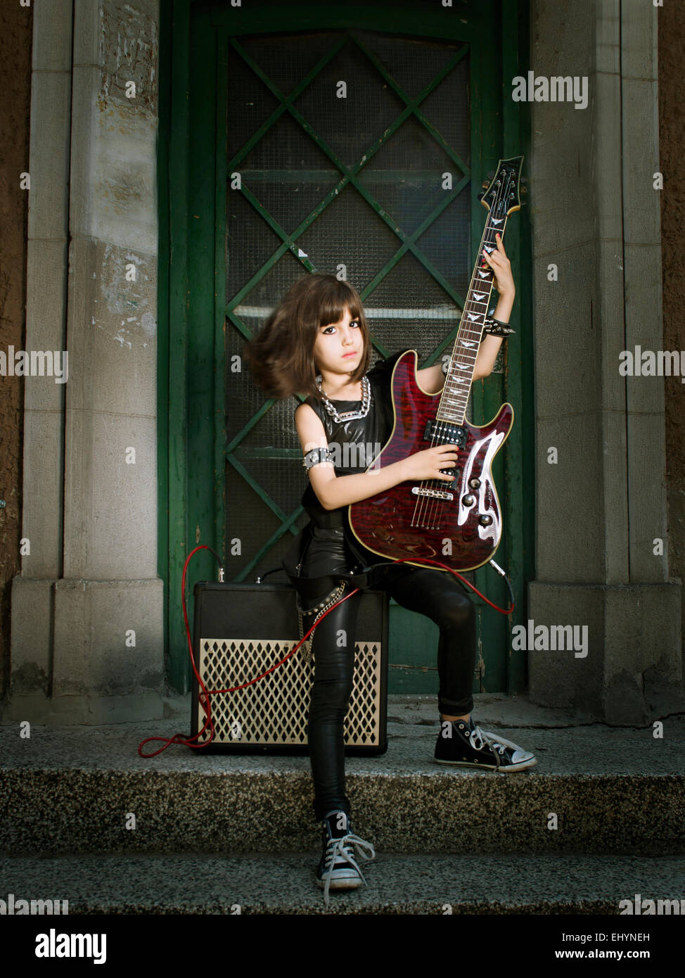 Girl dressed as a rock star playing the guitar - Stock Image