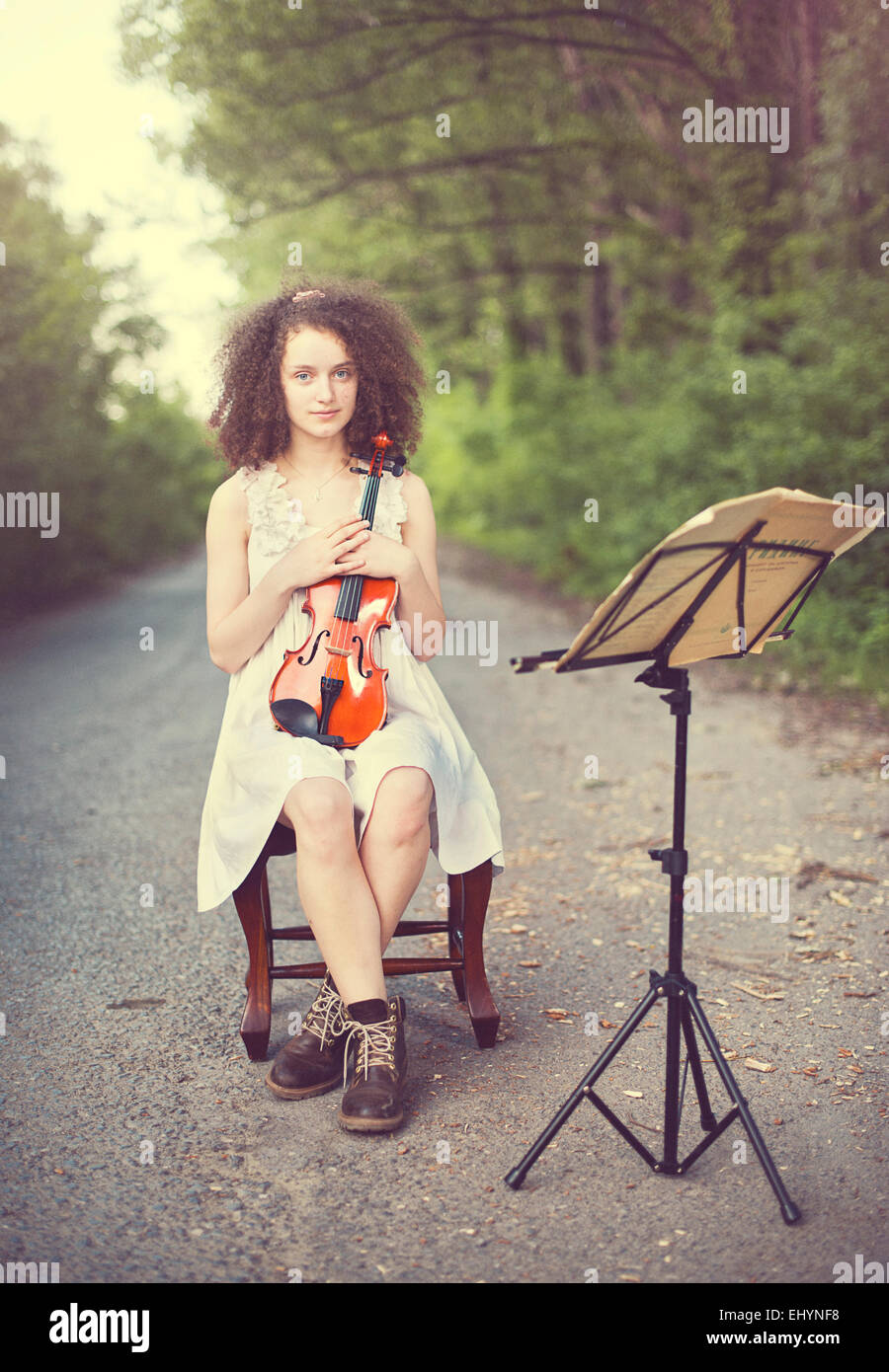 Portrait of a young woman sitting with her violin - Stock Image