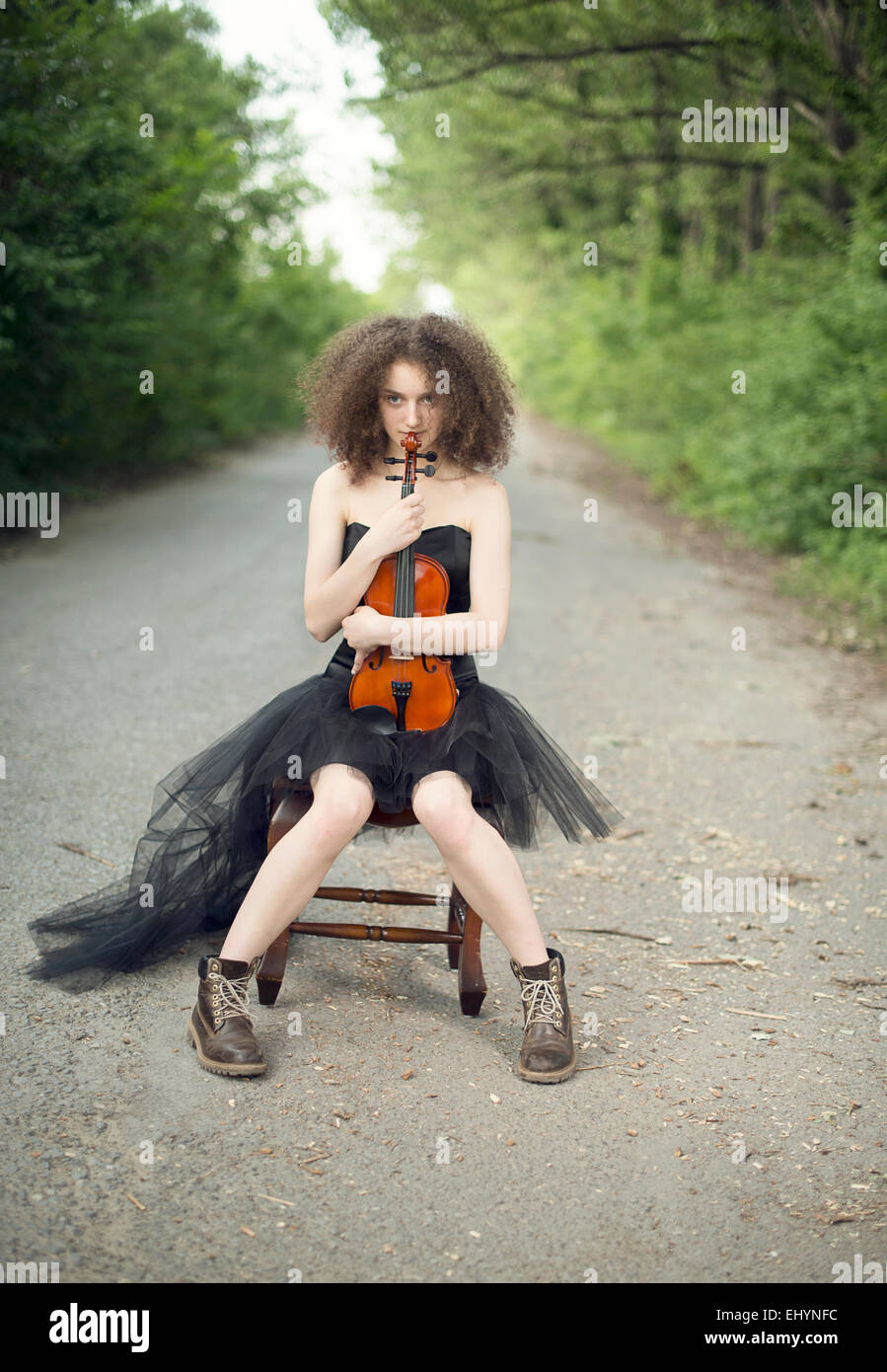 Young woman in a black dress sitting with her violin - Stock Image