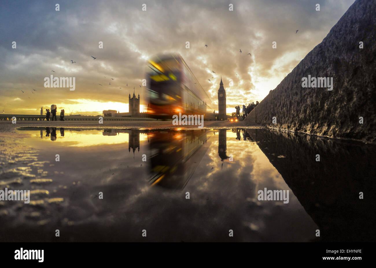 Bus driving across Westminster Bridge at sunset, England, UK Stock Photo