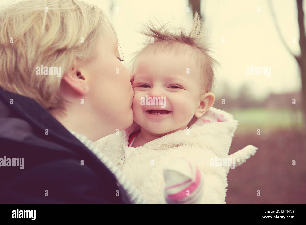Mother kissing baby girl - Stock Image