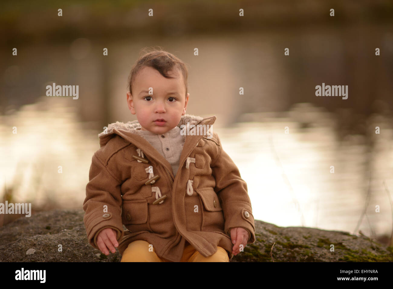 Baby boy sitting on a rock - Stock Image