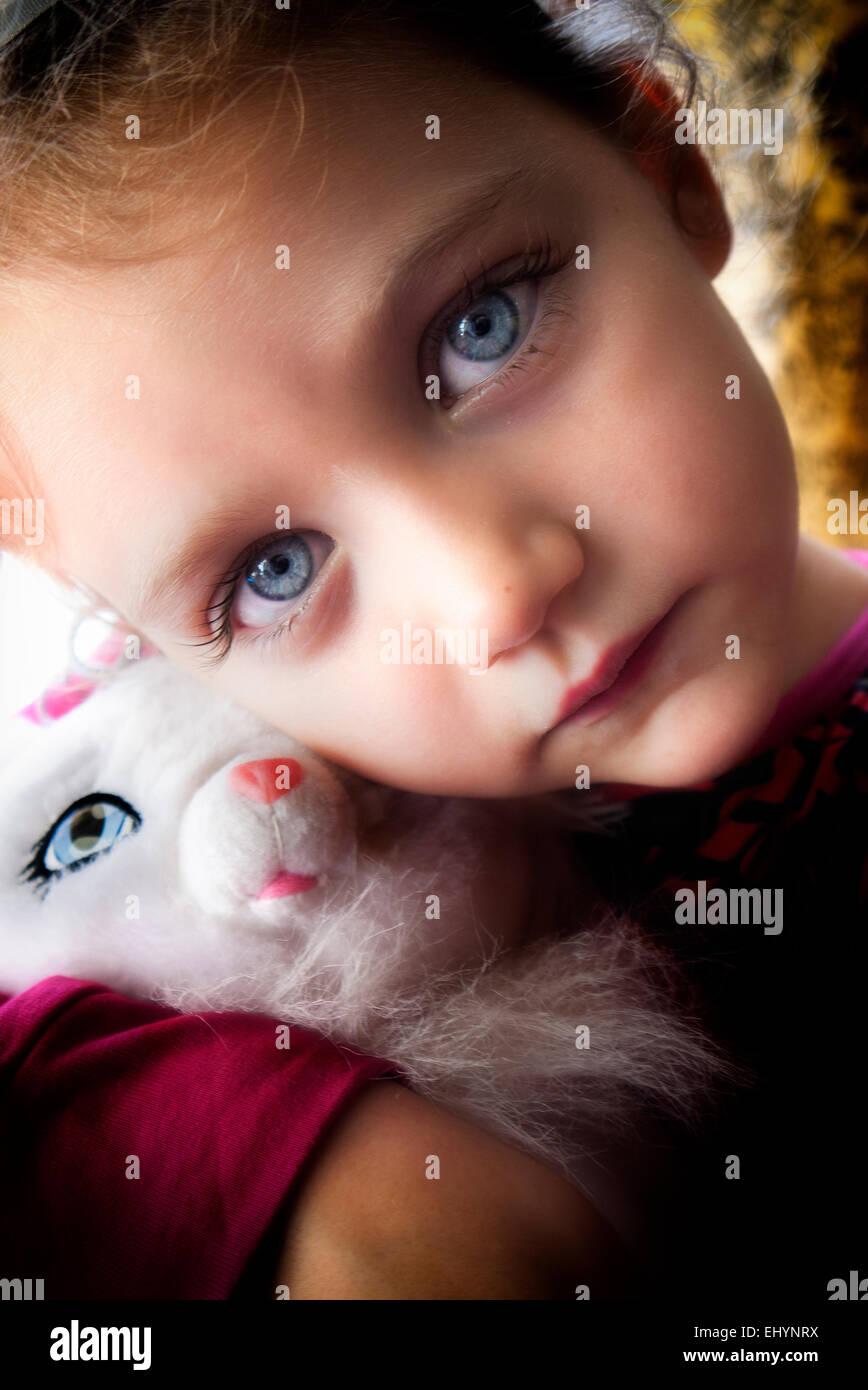 Girl cuddling kitten toy - Stock Image
