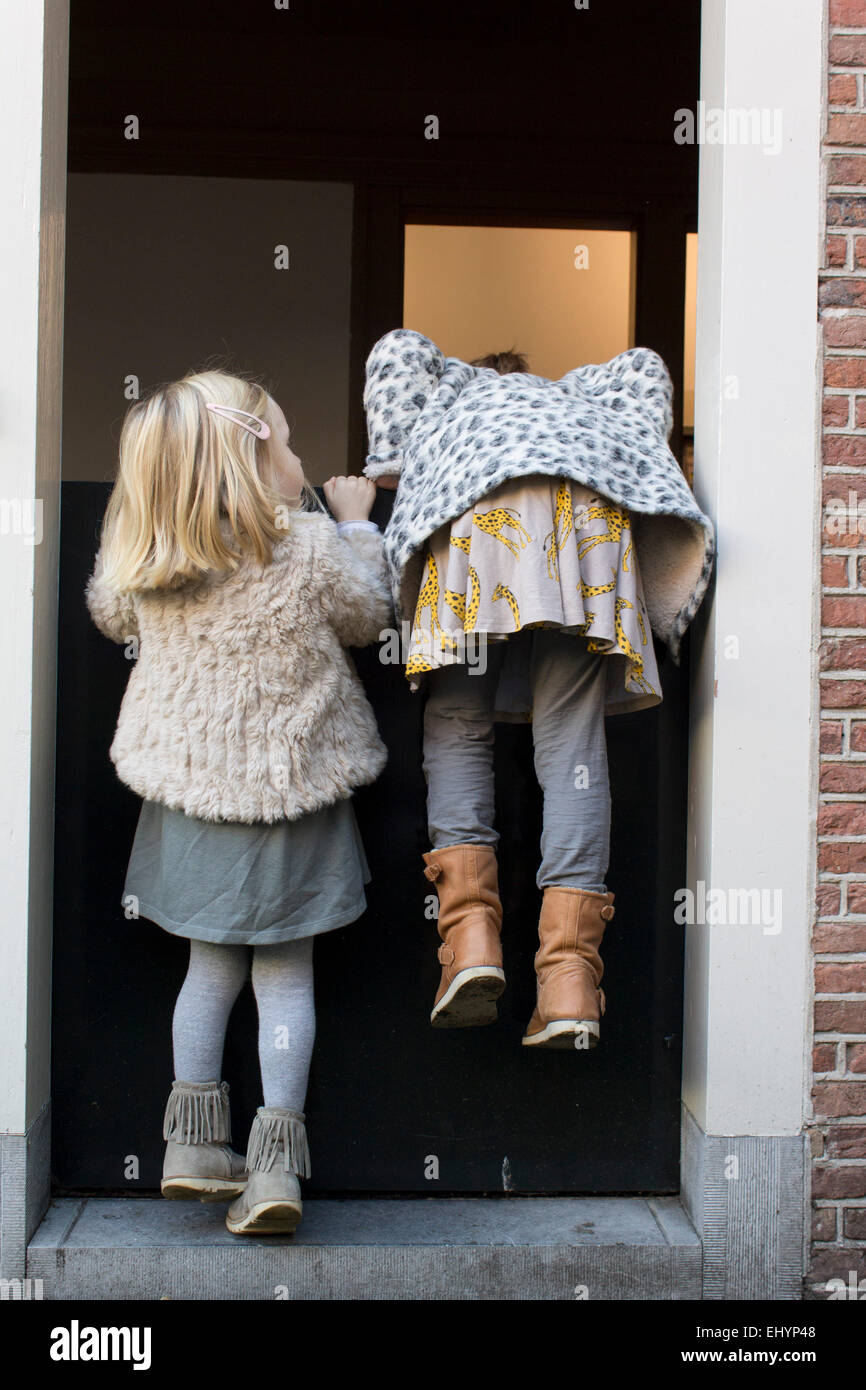Two girls trying to climb over a door - Stock Image