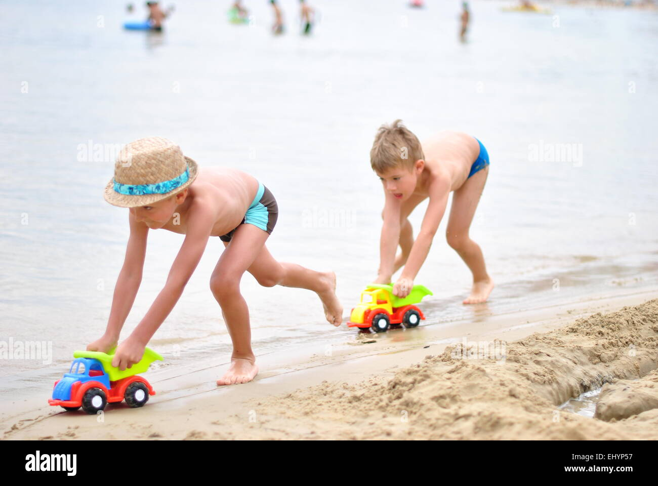 Boys playing with plastic cars on the beach - Stock Image