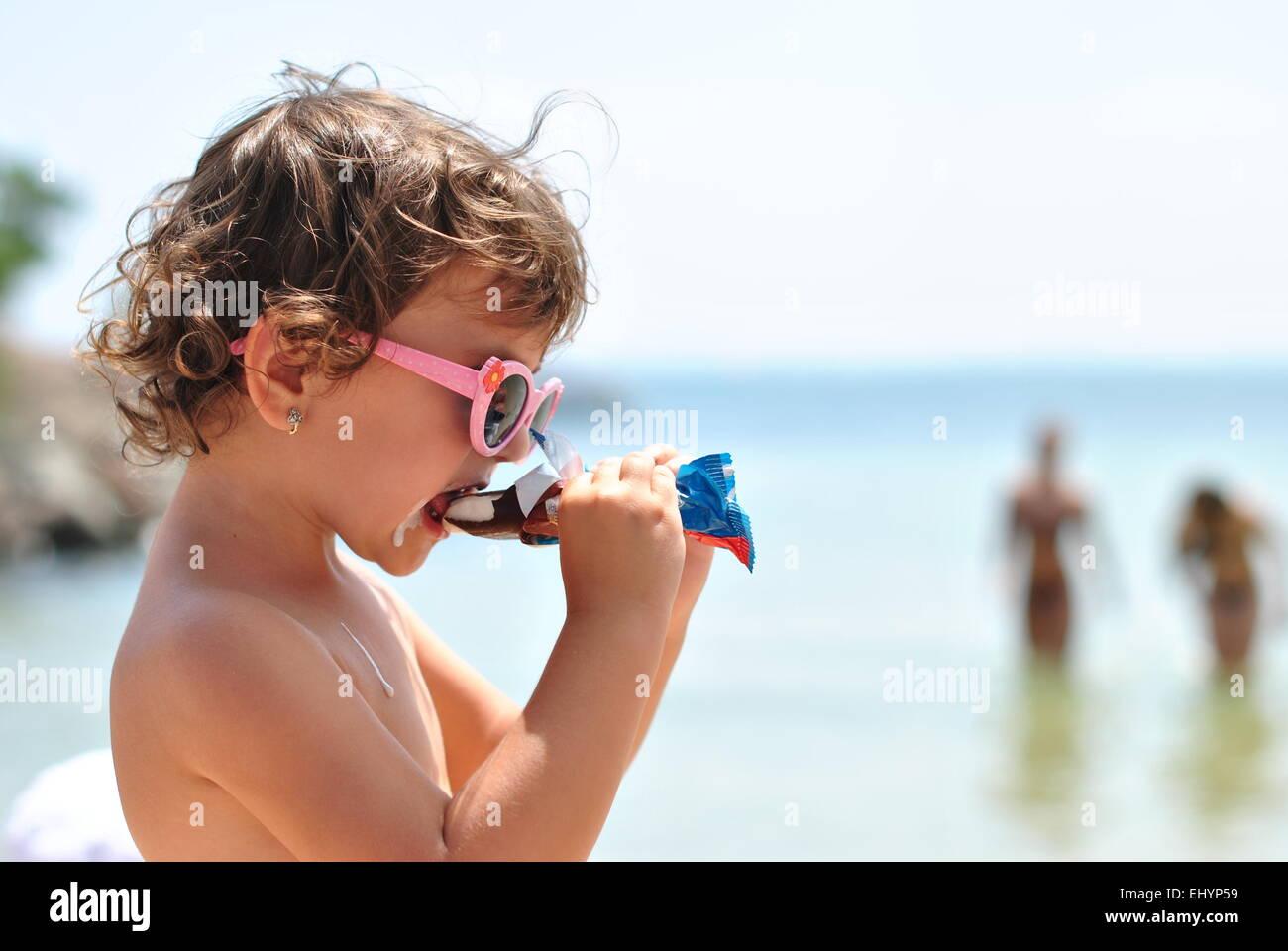 little girl eating ice cream on the beach of sea - Stock Image
