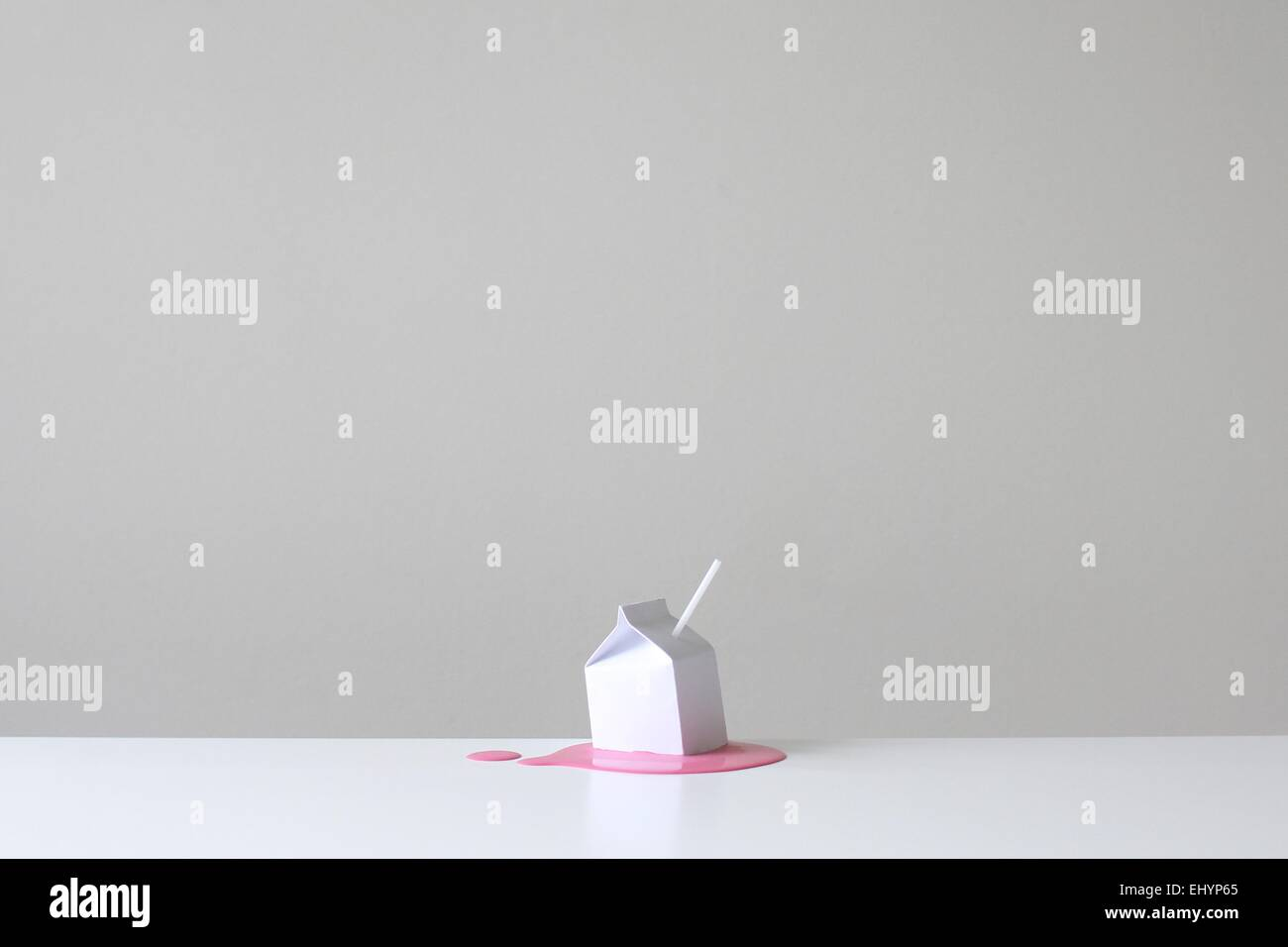 Conceptual milk carton with straw on a pool of pink strawberry millk - Stock Image