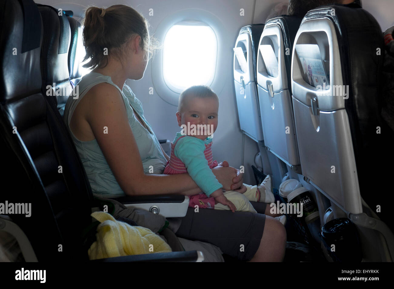 Mother with smiling baby travelling on aeroplane - Stock Image