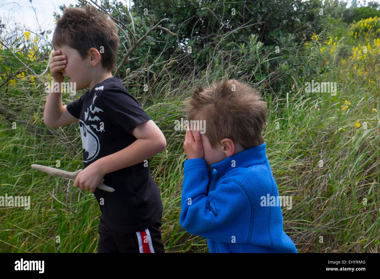 Children playing hide and seek in field - Stock Image