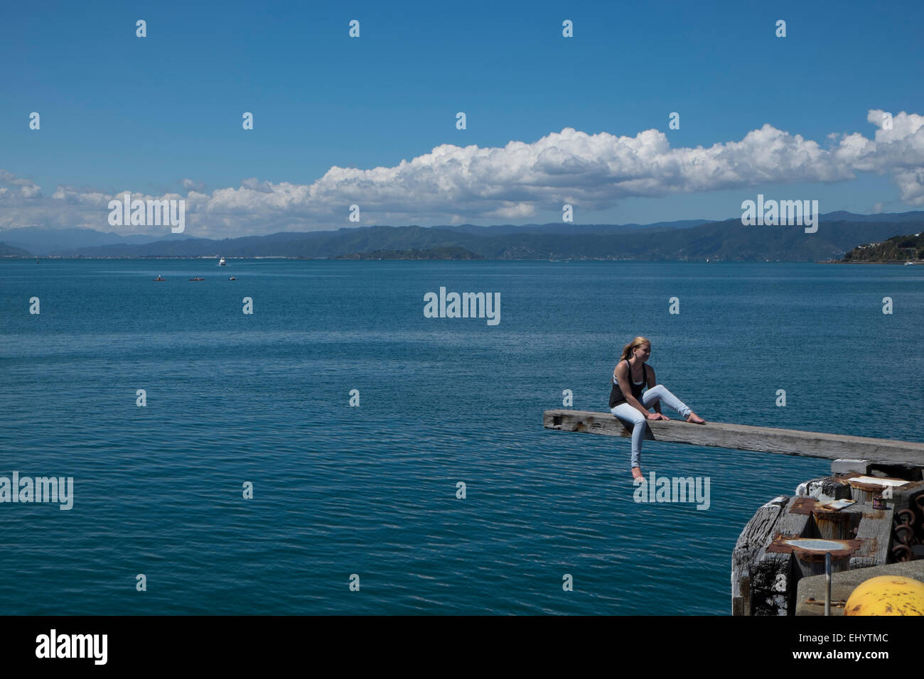 Woman sitting on wooden plank, Lambton Harbour, Wellington, North Island, New Zealand - Stock Image