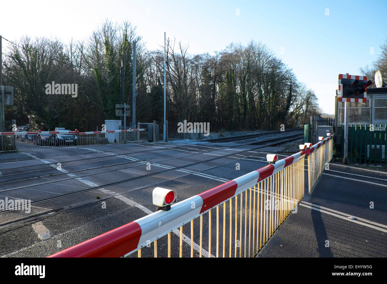 Gates closed at level crossing, railway line, St Fagan's, Cardiff, Wales, UK - Stock Image