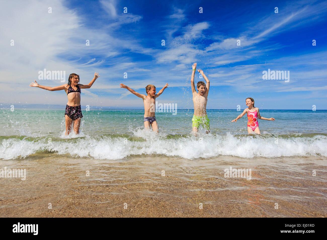 4, activity, swimming trunks, swim suit, joy, sky, hands, youngsters, boy, children, boy, coast, sea, girl, fun, - Stock Image