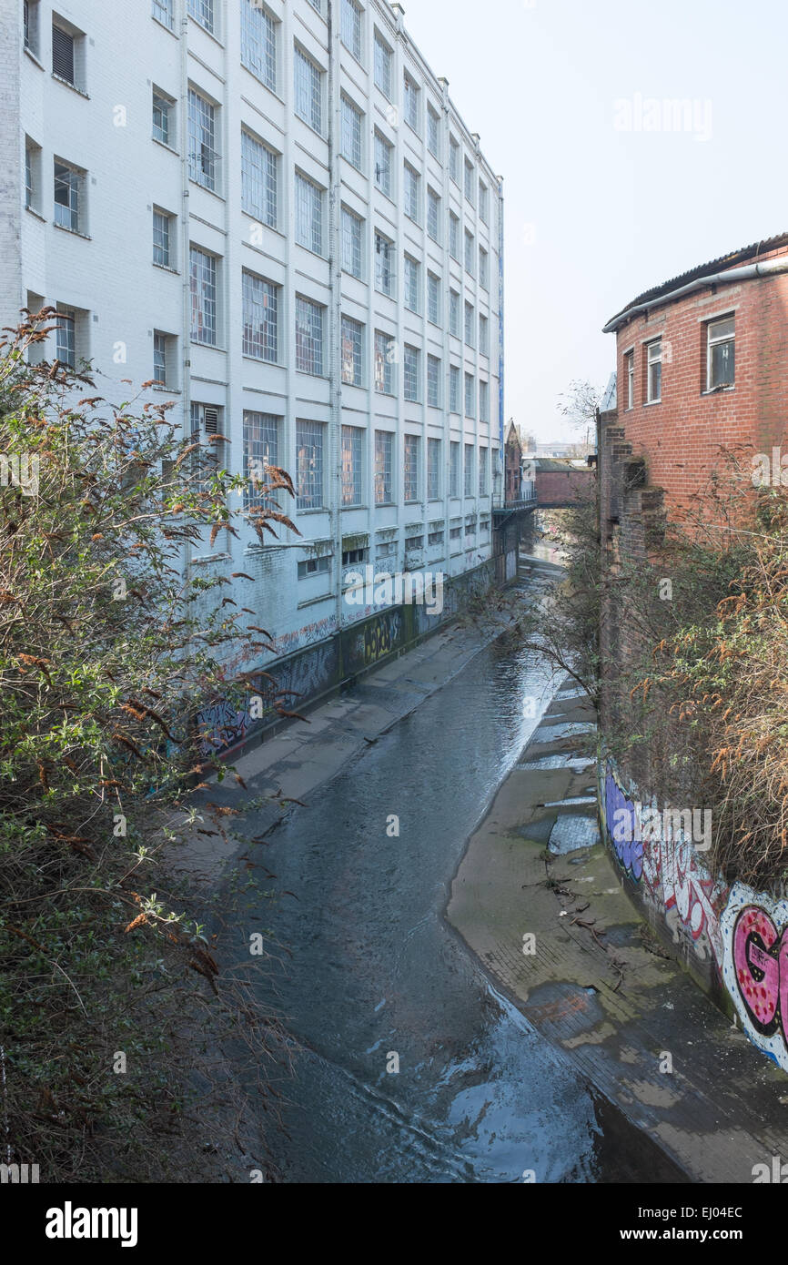 The River Rea flowing past buildings in the Custard Factory in Digbeth, Birmingham - Stock Image