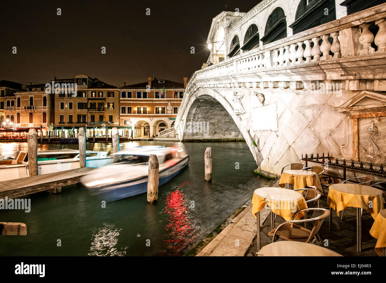 Pier with boat on the Grand Canal at the Rialto Bridge at night. - Stock Image