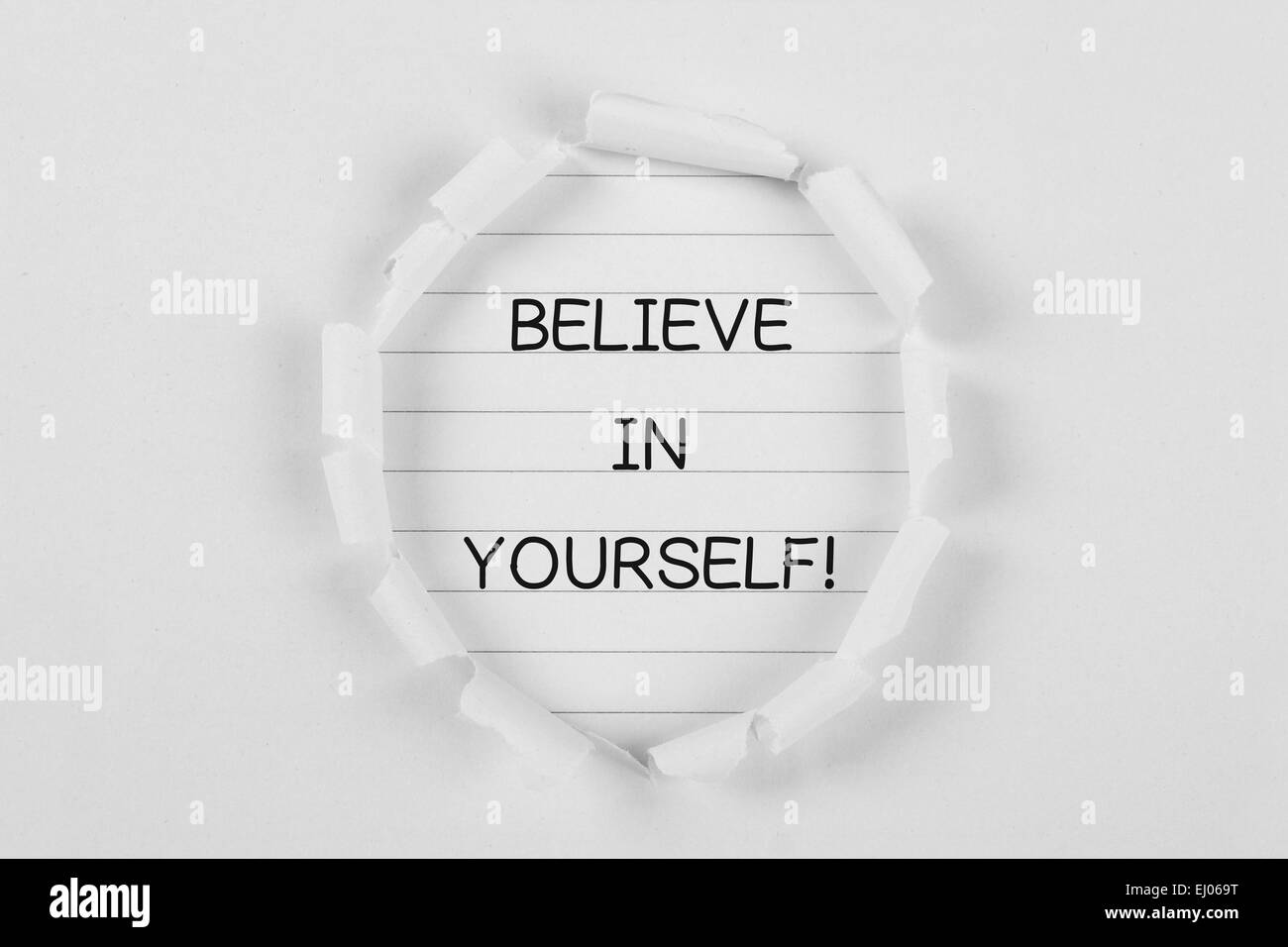 Believe in yourself on note paper with white tear paper. - Stock Image