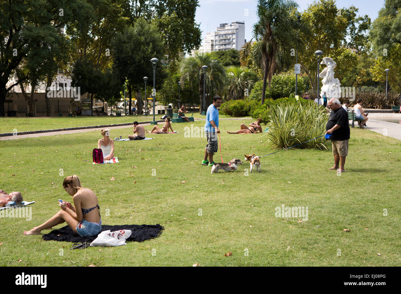 Argentina, Buenos Aires, Almagro, Parque Centenario, Centenary Park, people sunbathing on grass - Stock Image
