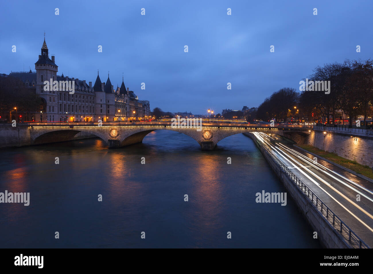 View of the Seine River by twilight from Pont Notre Dame, with the Conciergerie in the background. Paris, Ile de - Stock Image