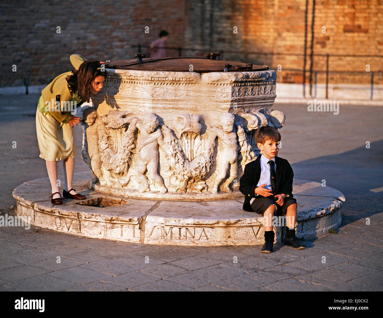 Venice, Veneto, Italy. Young boy and girl playing around a well head in Campo dei Frari. - Stock Image