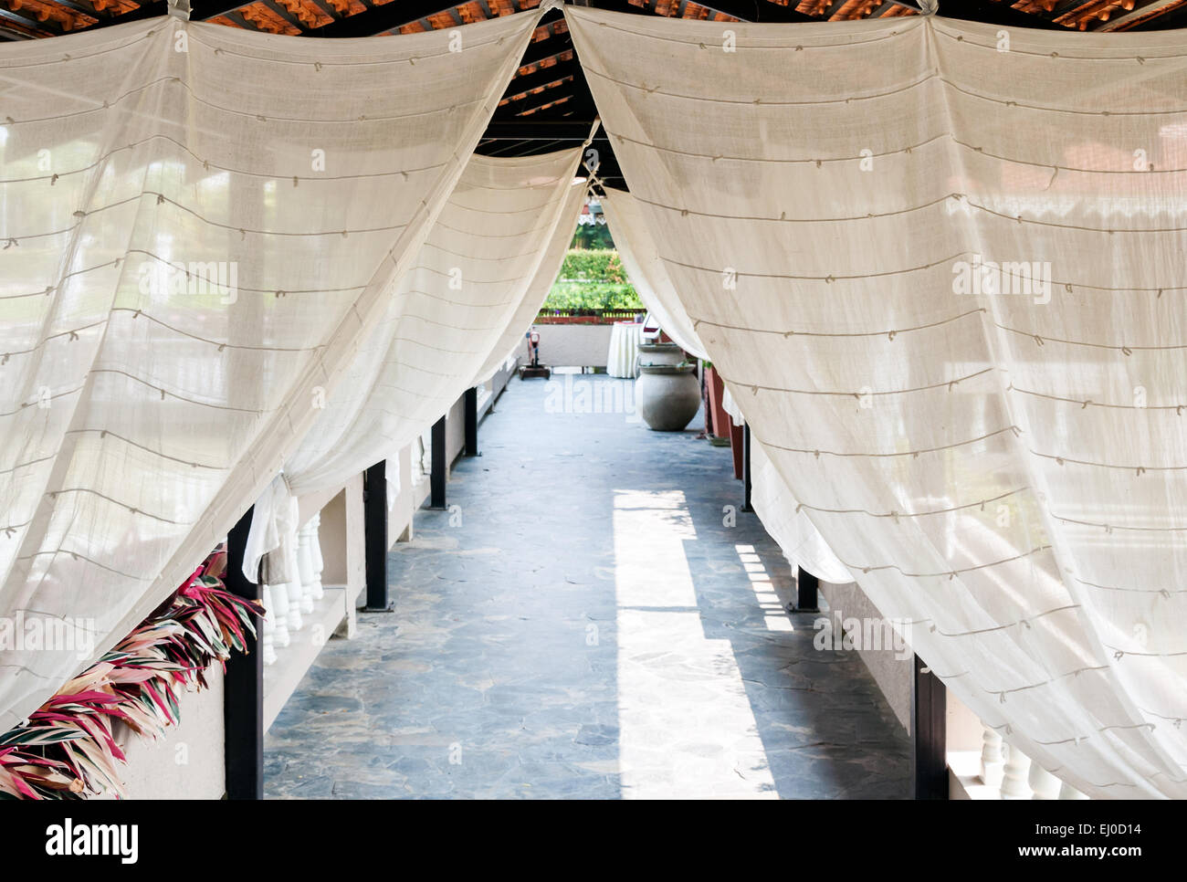 Clear white curtain along the pathway of restaurant. - Stock Image