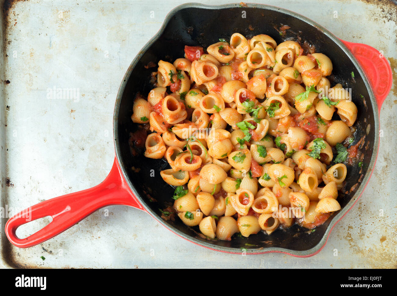 Gomiti elbow pasta shells in arrabbiata tomato, garlic and chili sauce, garnished with chopped parsley, cooking - Stock Image