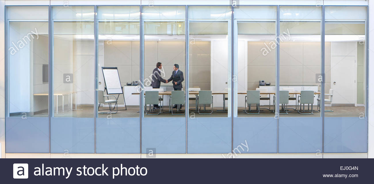 View through window, of business men shaking hands in meeting room - Stock Image