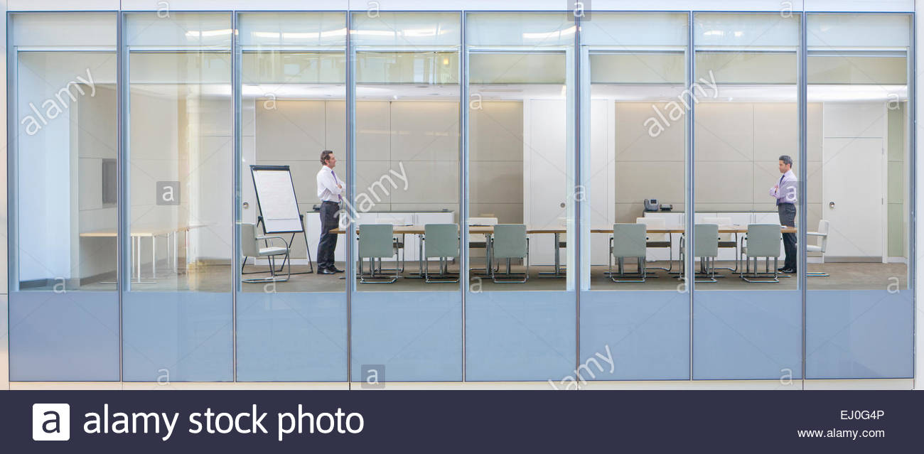 View through window, of business men in meeting room - Stock Image