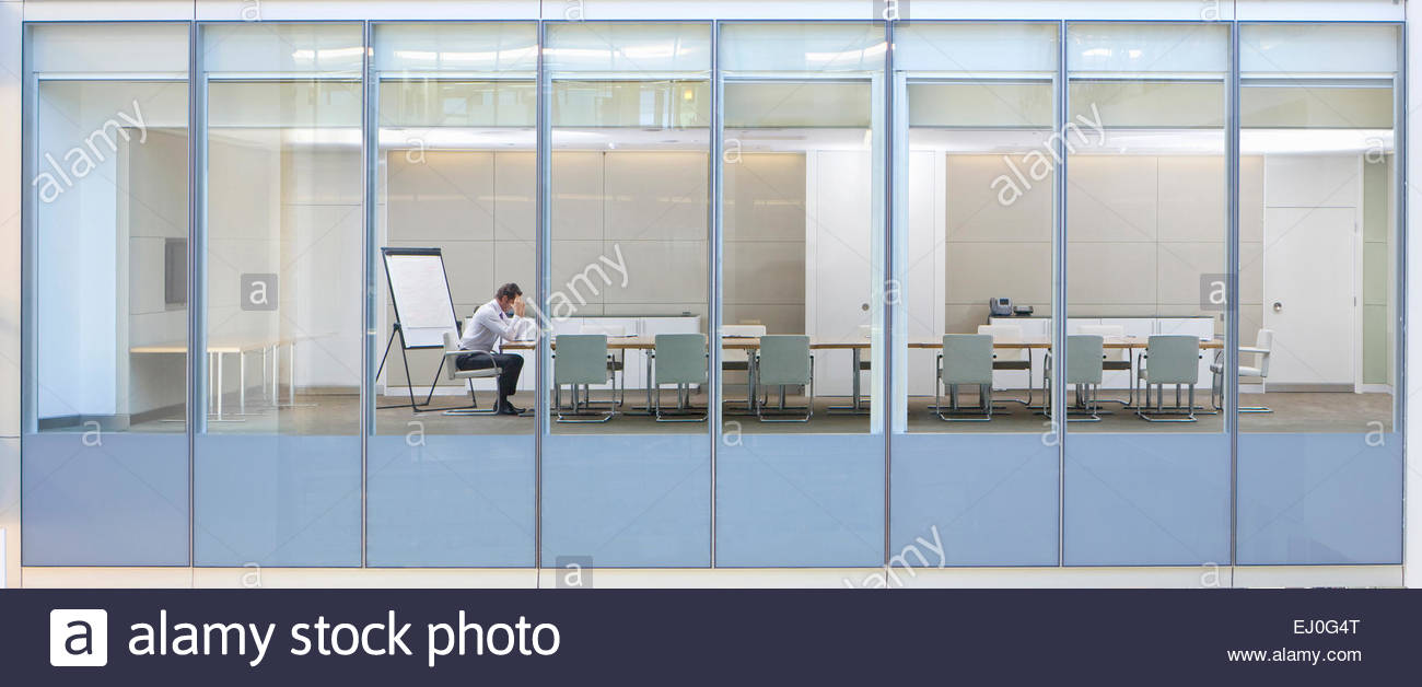 View through window, of business man in meeting room - Stock Image