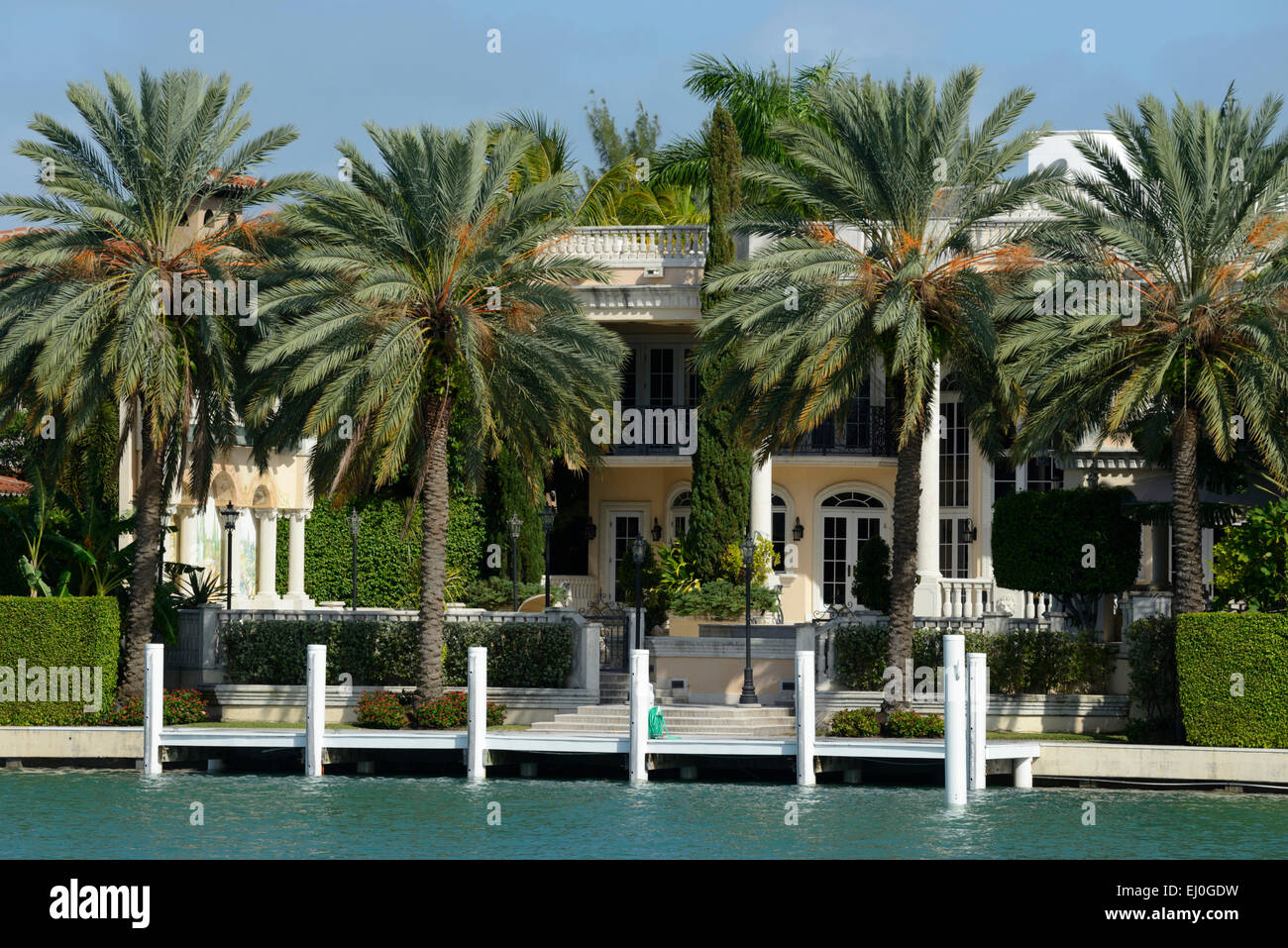 USA, Florida, Dade County, Miami Beach, mansion on waterfront with palm trees, - Stock Image