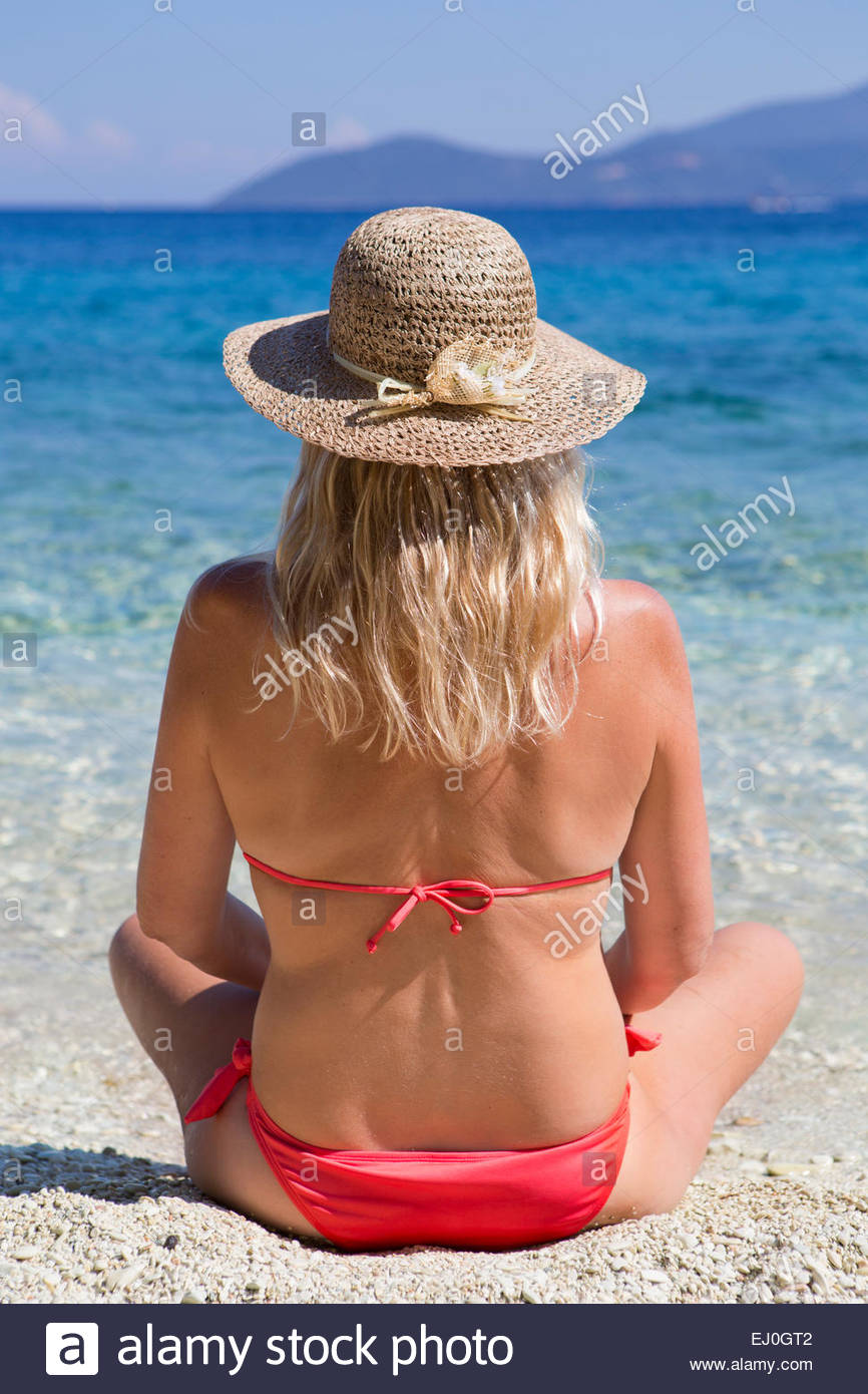 woman, looking out to sea, sitting on sunny beach Stock Photo