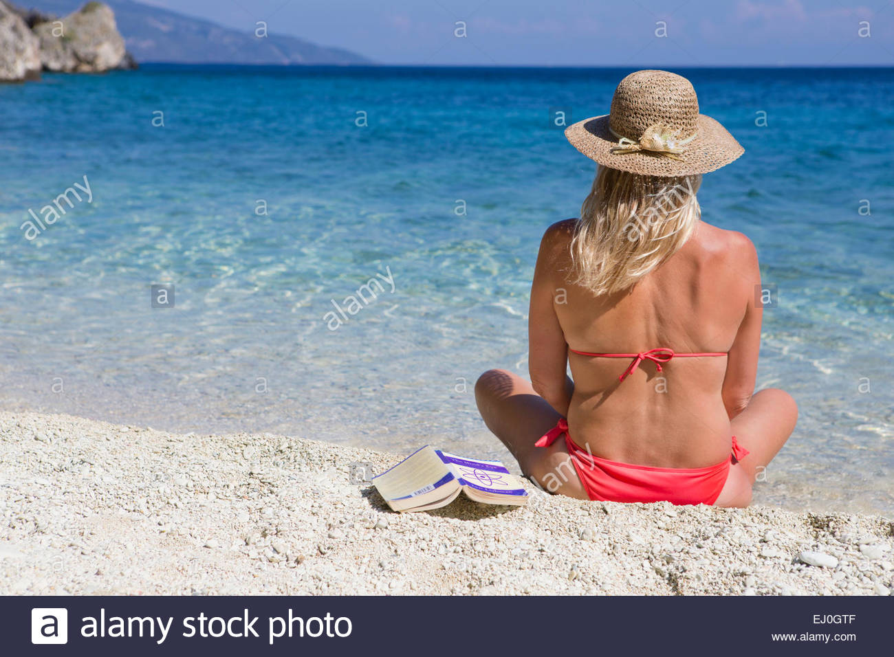 woman, looking out to sea, sitting on sunny beach - Stock Image