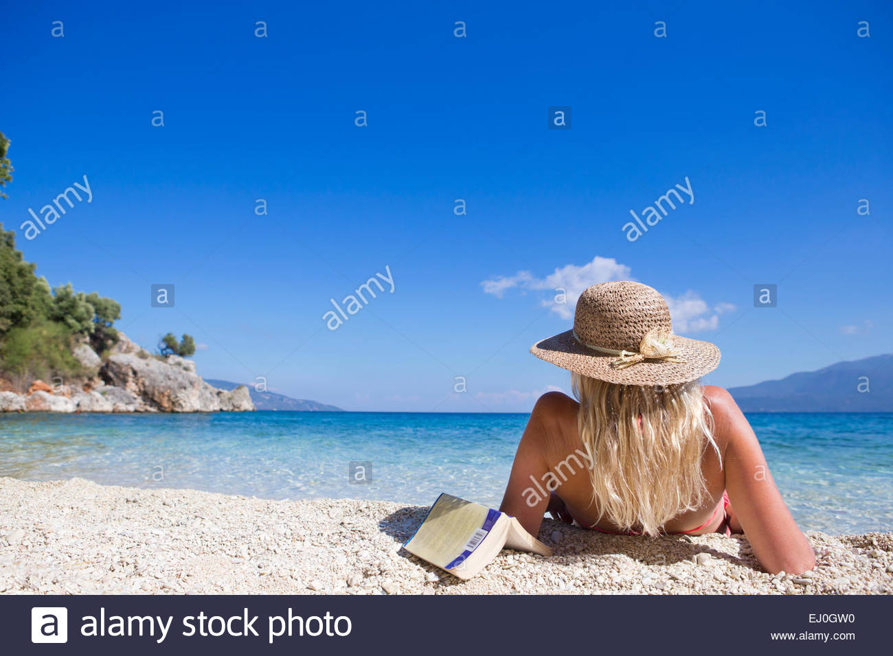 woman, looking out to sea, lying on beach with book - Stock Image