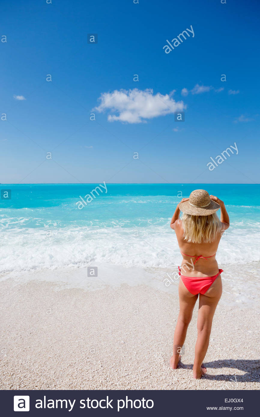 woman, looking out to sea, standing on sunny beach - Stock Image