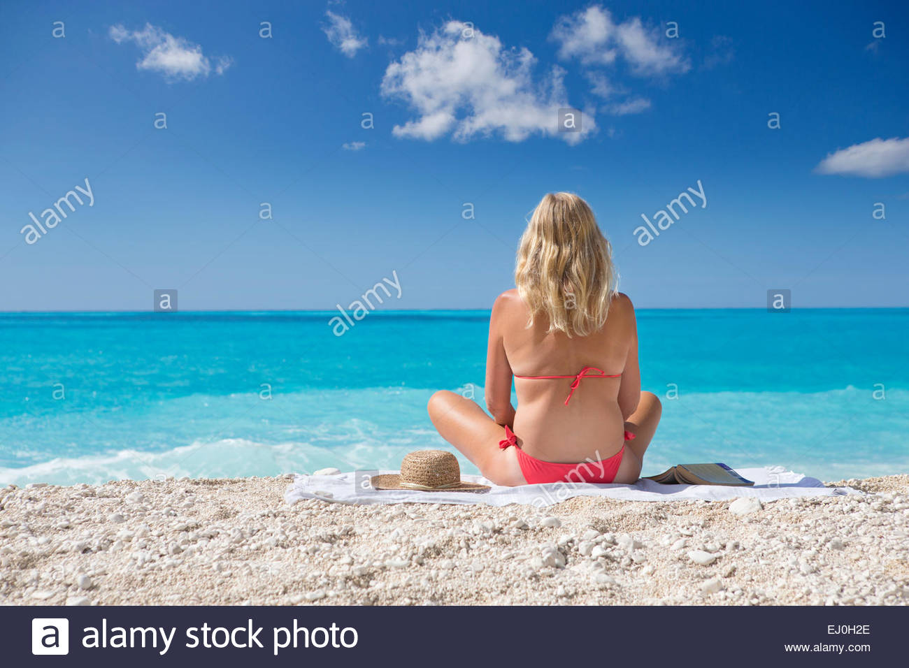 woman, looking out to sea, sitting on towel on sunny beach - Stock Image