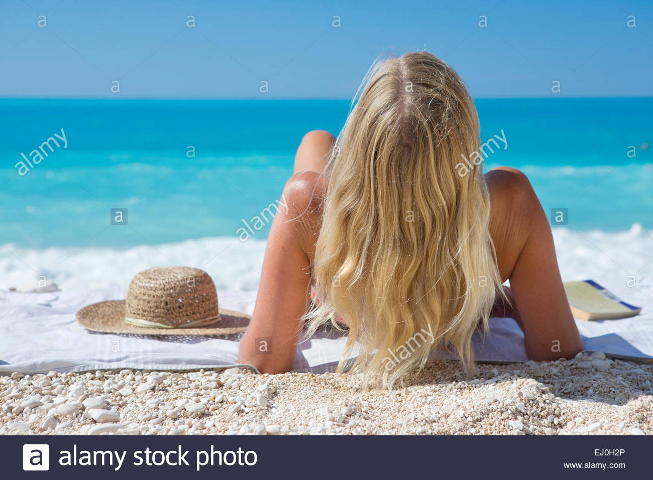 woman, looking out to sea, lying on towel on sunny beach - Stock Image