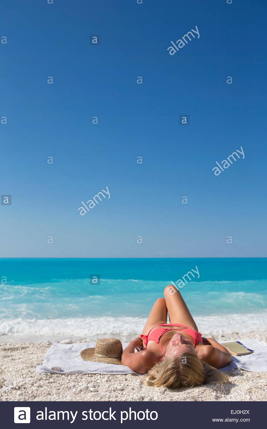 woman, lying on towel on sunny beach - Stock Image