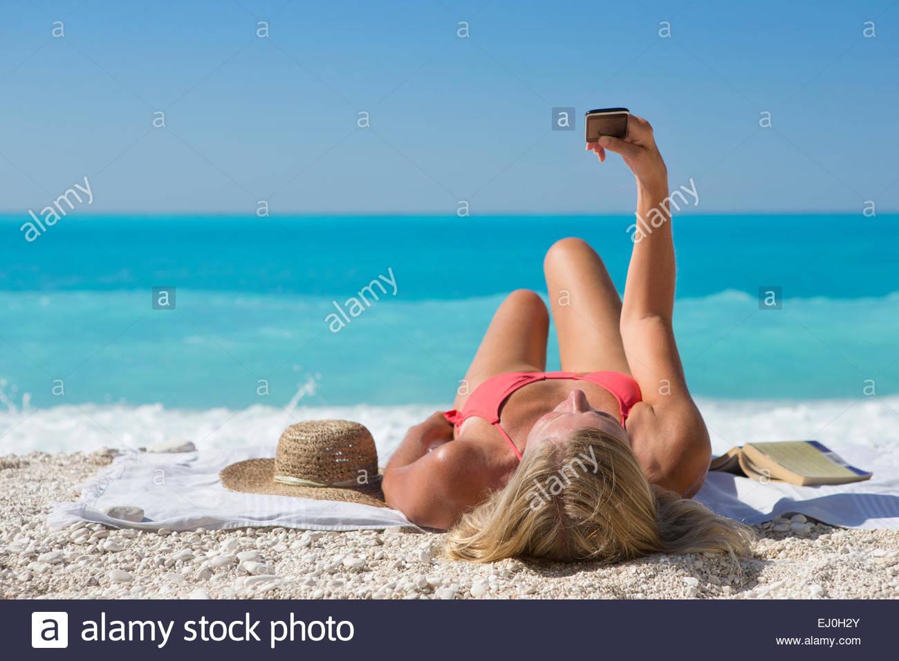 woman, taking selfie, lying on towel on sunny beach - Stock Image