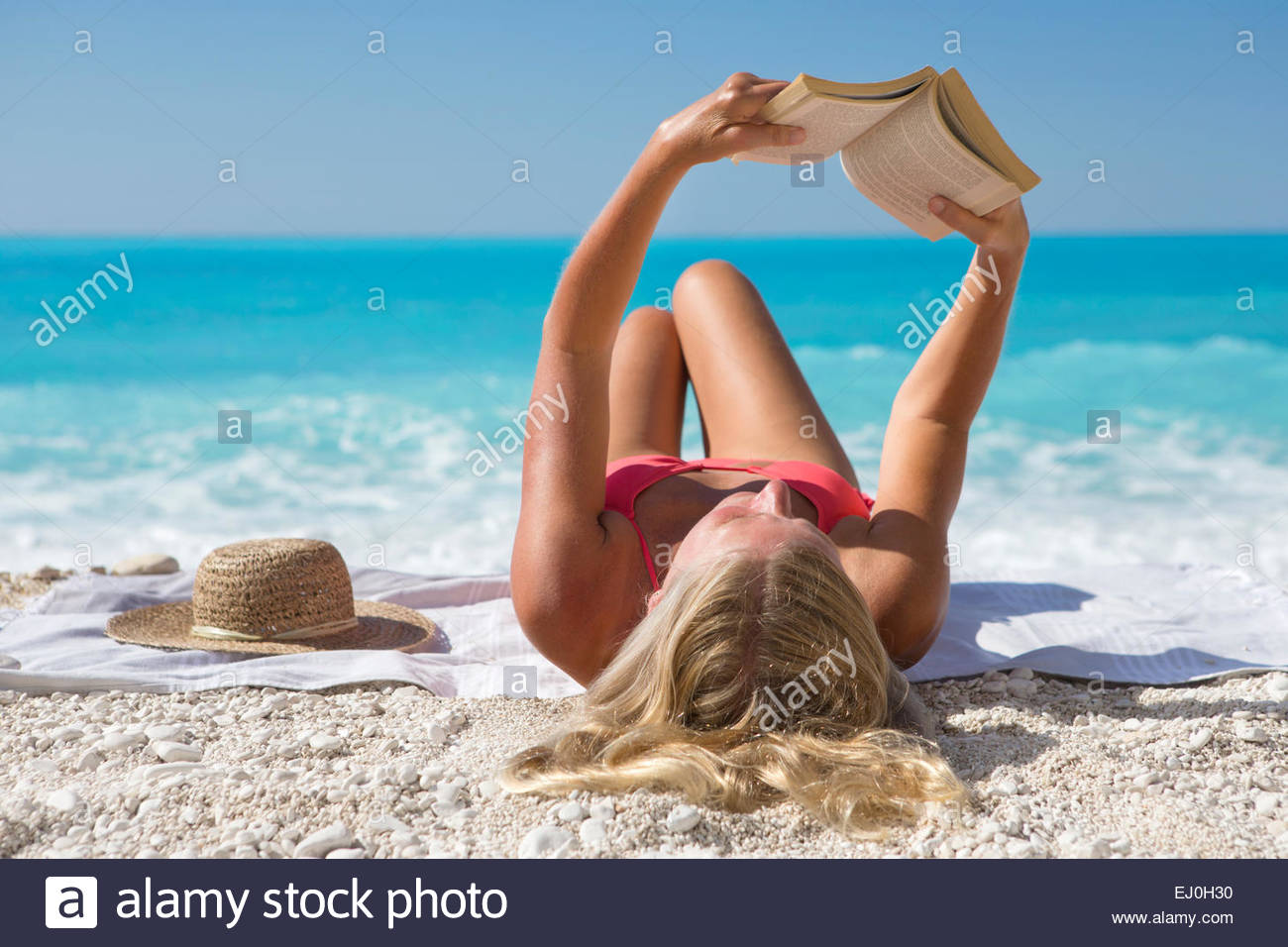 woman, reading book, lying on towel on sunny beach - Stock Image