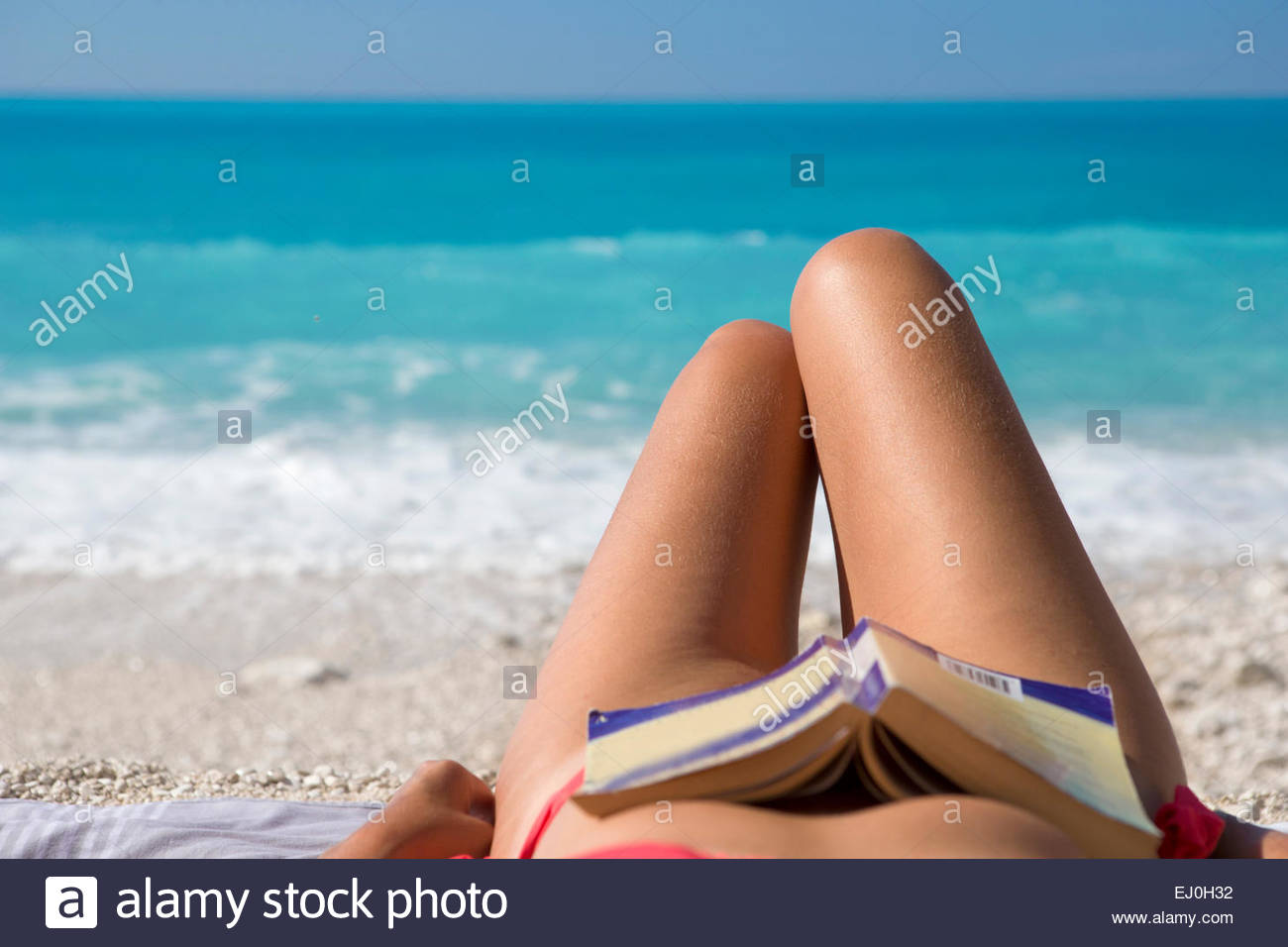 woman, with book resting on stomach, lying on towel on sunny beach - Stock Image