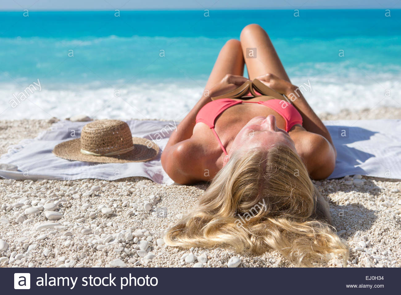 woman, holding book, lying on towel on sunny beach - Stock Image