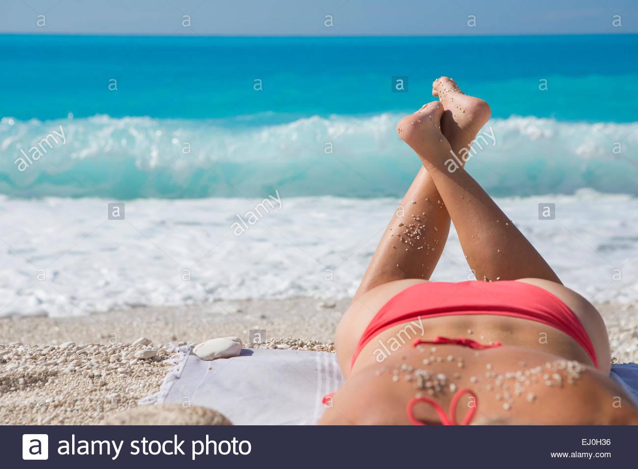 woman, sunbathing with sand on back, on sunny beach - Stock Image