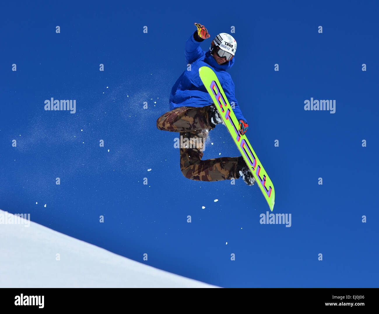 VERBIER, SWITZERLAND - FEBRUARY 21: Freestyle snowboarder performing rear grab stunt and trailing snow:  February - Stock Image