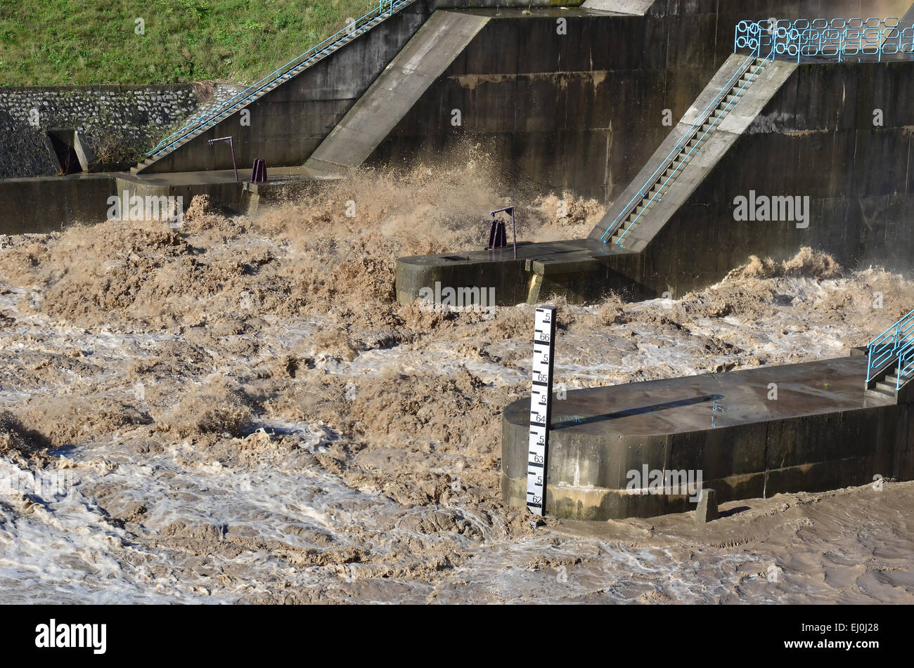 Flood water bursting over a dam, after extremely high rainfall, possibly caused by climate change. - Stock Image