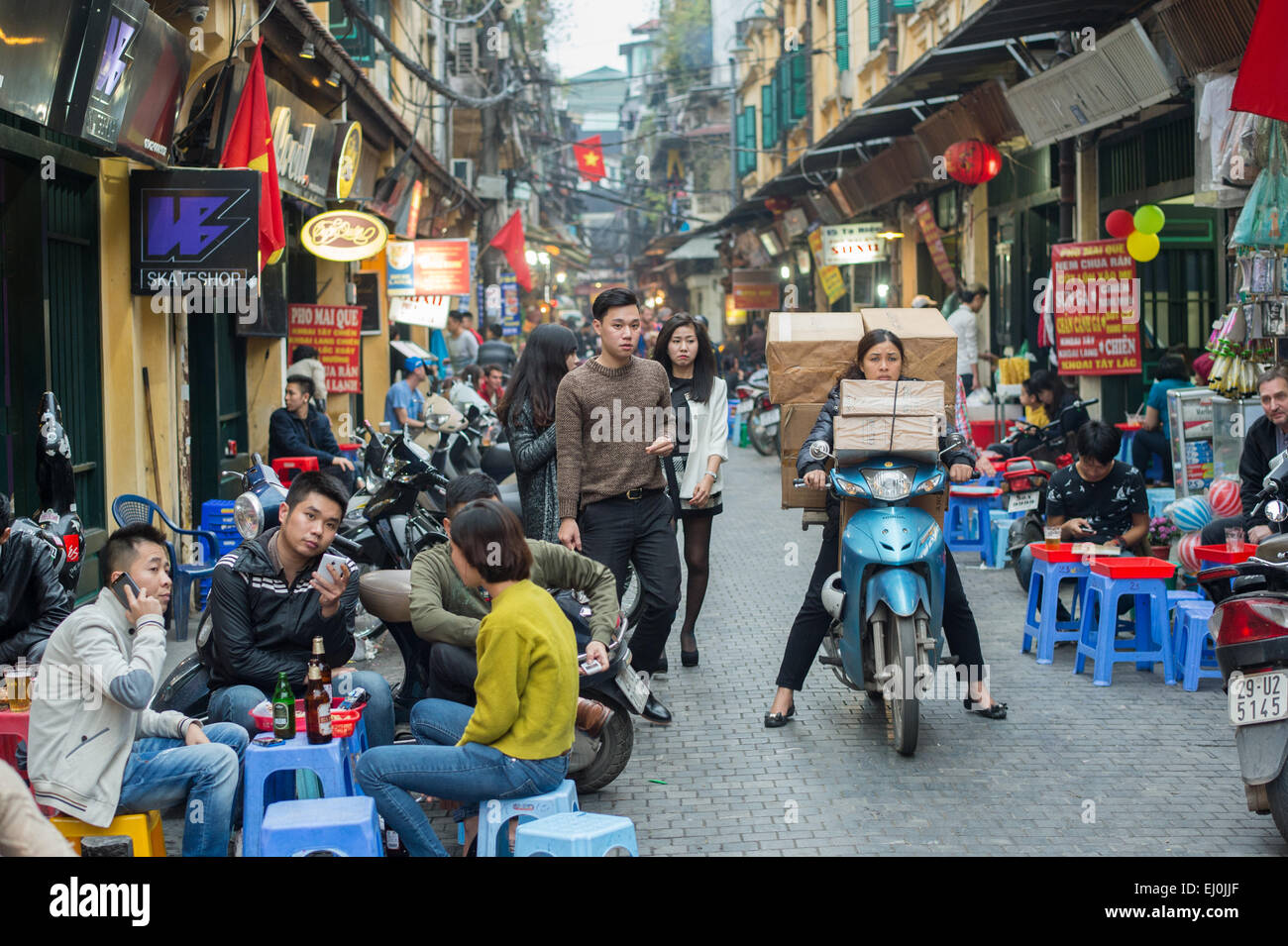 Vietnamese woman transports a huge load on a motorbike in the old quarter of Hanoi. - Stock Image