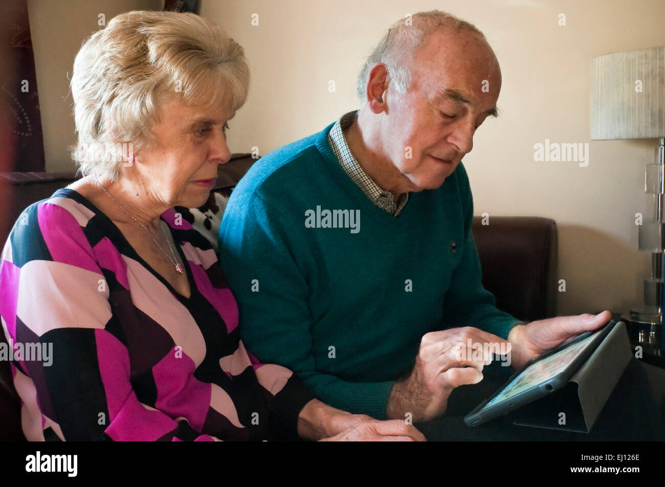 Horizontal portrait of an elderly couple using an ipad together. - Stock Image