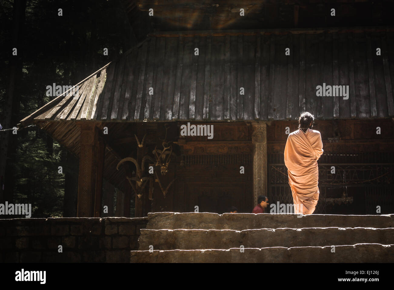 Silhouette of a monk walking into a temple in Manali, India - Stock Image