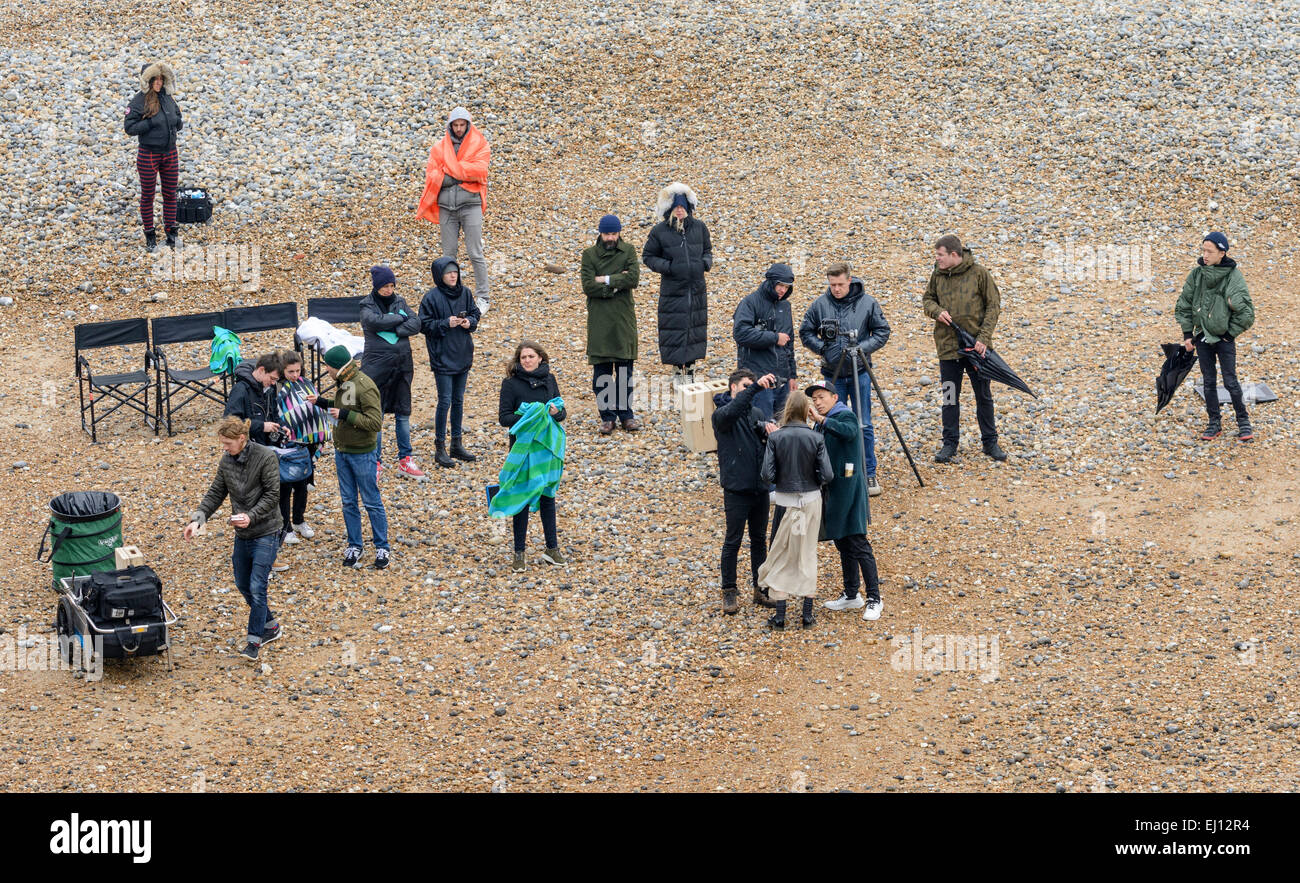 Group of staff and a model assembled on a beach for a professional photo shoot. - Stock Image