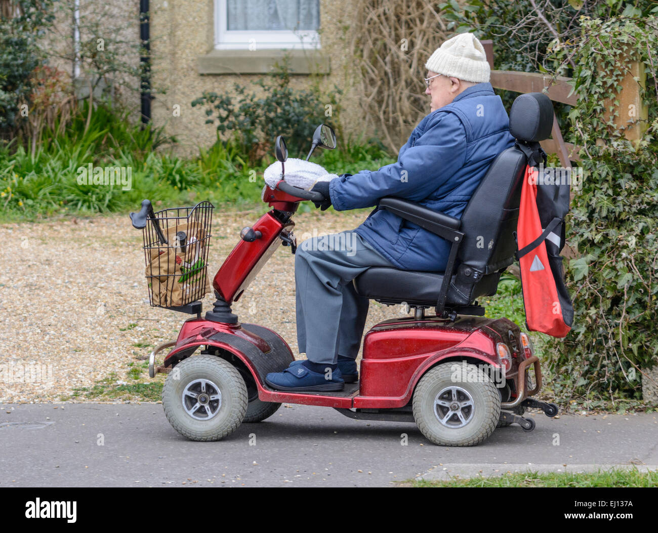 Mobility scooter - Electric mobility scooter being ridden by an elderly man along a pavement. - Stock Image